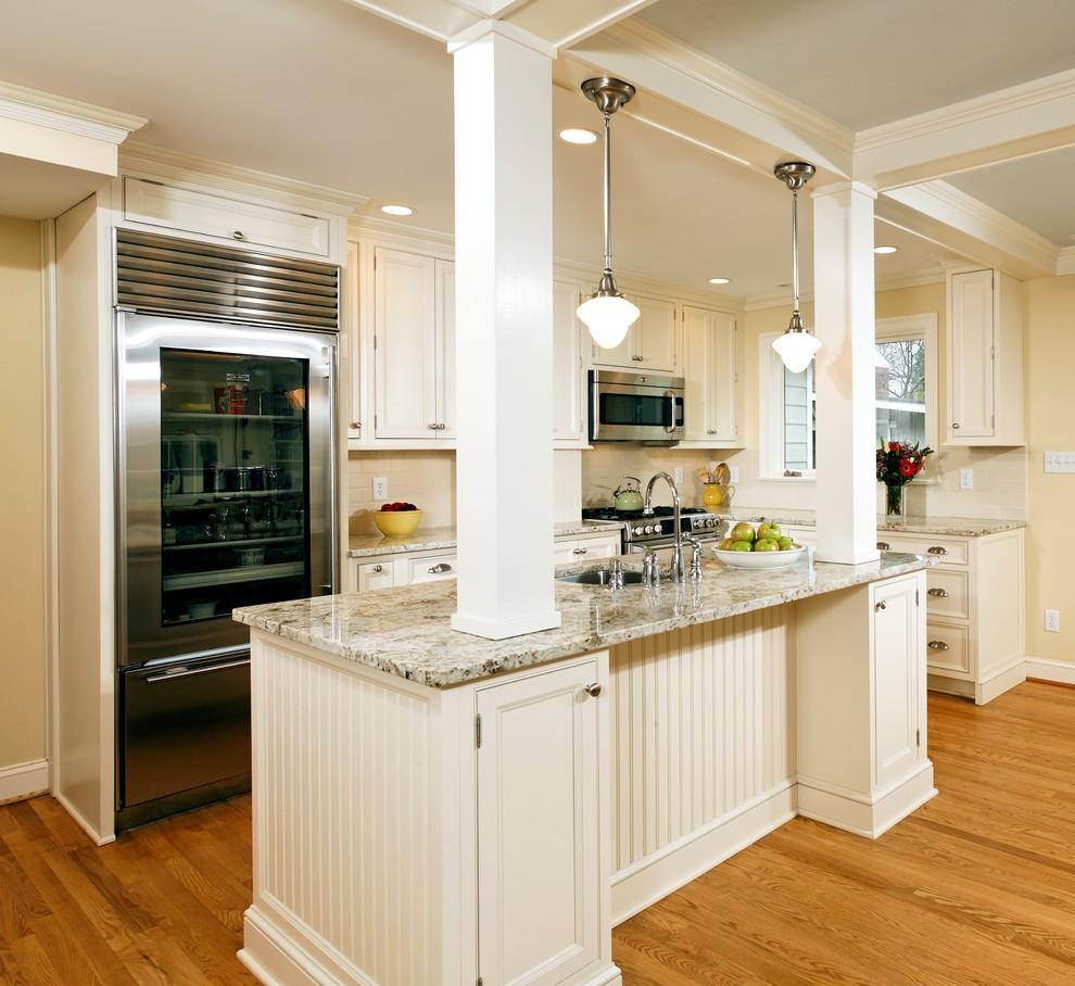 Diseño de cocinas en L clásica con electrodomésticos de acero inoxidable, armarios con paneles empotrados y puertas de armario blancas