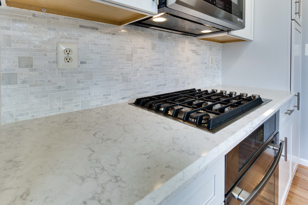 Example of a small transitional galley medium tone wood floor kitchen design in DC Metro with an undermount sink, shaker cabinets, white cabinets, quartz countertops, stainless steel appliances and an island