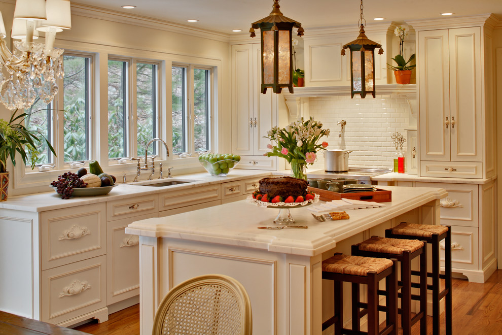 Example of a cottage chic kitchen design in New York with recessed-panel cabinets, stainless steel appliances, subway tile backsplash, an undermount sink, white cabinets, marble countertops and white backsplash