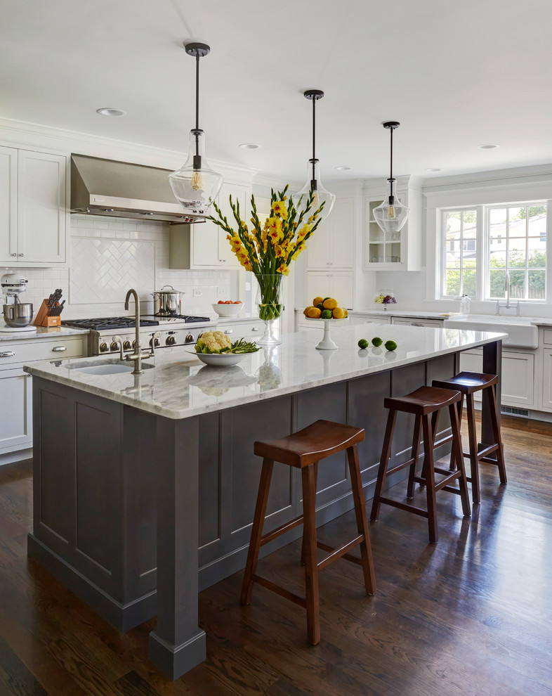Inspiration for a large transitional dark wood floor eat-in kitchen remodel in Chicago with a single-bowl sink, recessed-panel cabinets, white cabinets, marble countertops, white backsplash, subway tile backsplash, stainless steel appliances and an island