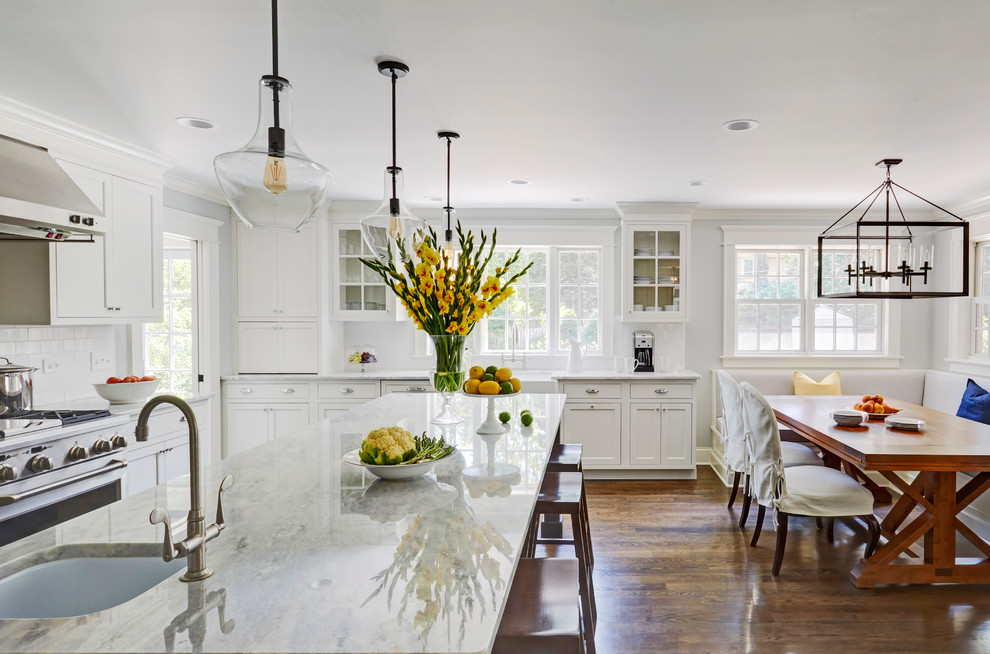 Example of a large transitional dark wood floor eat-in kitchen design in Chicago with a single-bowl sink, recessed-panel cabinets, white cabinets, marble countertops, white backsplash, subway tile backsplash, stainless steel appliances and an island