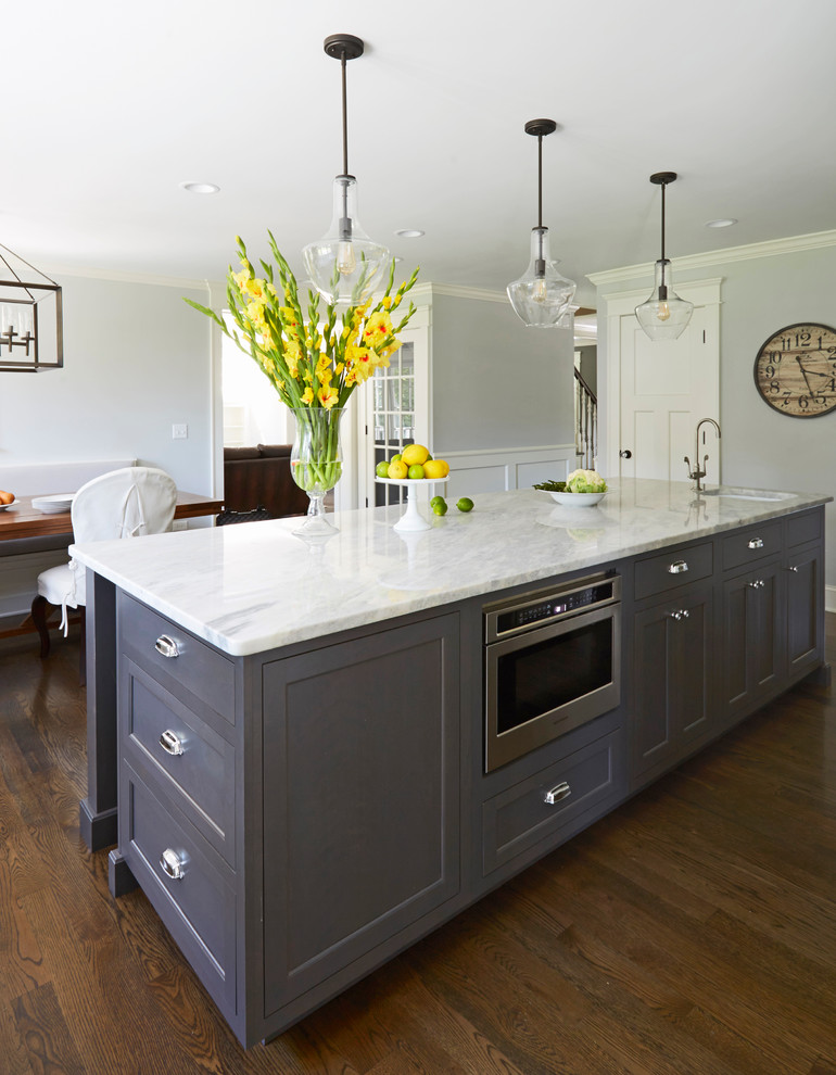 Inspiration for a large transitional l-shaped dark wood floor eat-in kitchen remodel in Chicago with a single-bowl sink, recessed-panel cabinets, white cabinets, marble countertops, white backsplash, subway tile backsplash, stainless steel appliances and an island