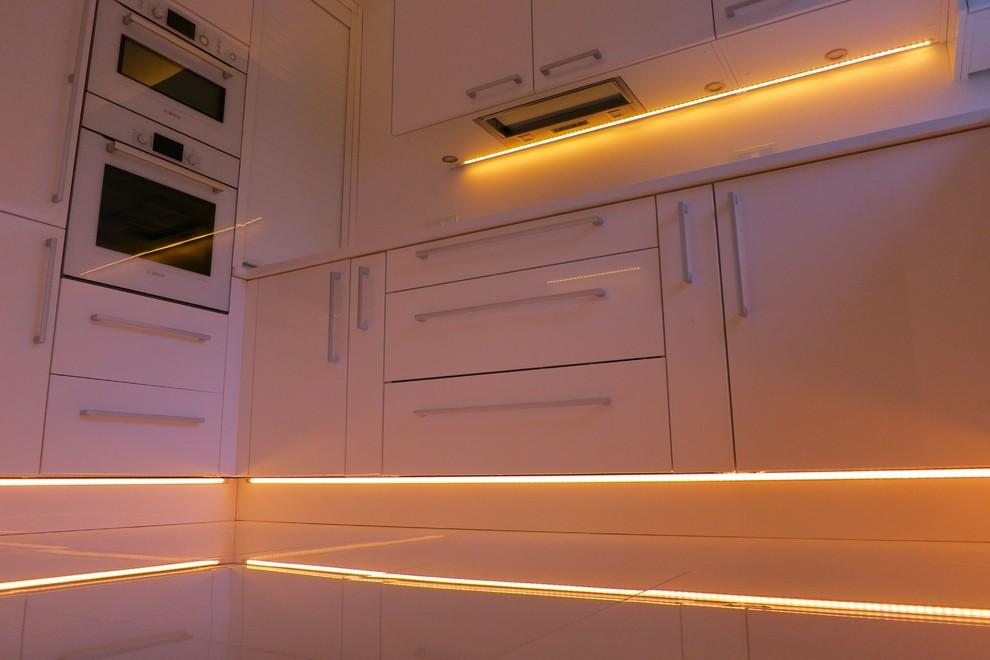 Immagine di una piccola cucina ad U moderna chiusa con lavello sottopiano, ante lisce, ante bianche, top in quarzite, paraspruzzi bianco, paraspruzzi con lastra di vetro, elettrodomestici bianchi, pavimento con piastrelle in ceramica e nessuna isola