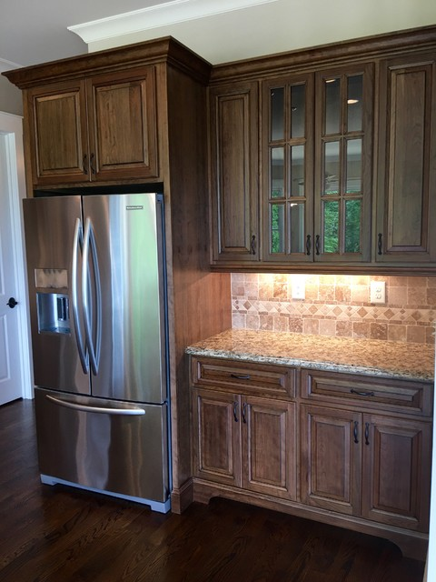 Large transitional l-shaped dark wood floor kitchen photo in Atlanta with an undermount sink, raised-panel cabinets, medium tone wood cabinets, granite countertops, beige backsplash, mosaic tile backsplash, stainless steel appliances and an island