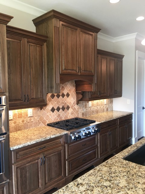 Example of a large transitional l-shaped dark wood floor kitchen design in Atlanta with an undermount sink, raised-panel cabinets, medium tone wood cabinets, granite countertops, beige backsplash, mosaic tile backsplash, stainless steel appliances and an island