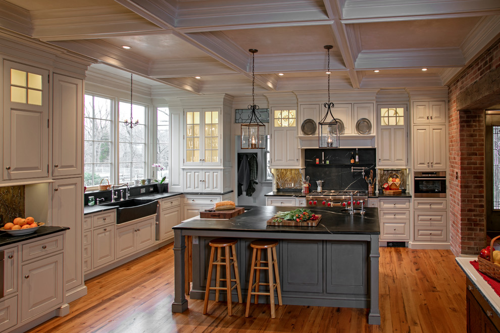 Eat-in kitchen - large farmhouse l-shaped medium tone wood floor eat-in kitchen idea in New York with an integrated sink, beaded inset cabinets, white cabinets, soapstone countertops, black backsplash, stone slab backsplash, paneled appliances and an island