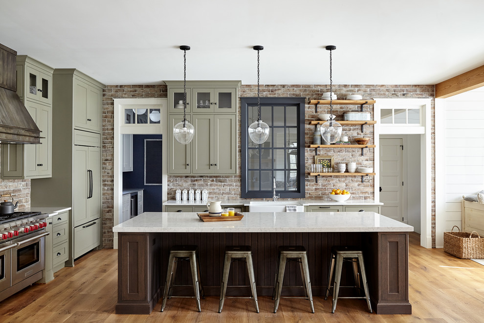 Open concept kitchen - large cottage light wood floor and beige floor open concept kitchen idea in Philadelphia with a farmhouse sink, shaker cabinets, quartz countertops, red backsplash, brick backsplash, paneled appliances, an island, green cabinets and white countertops