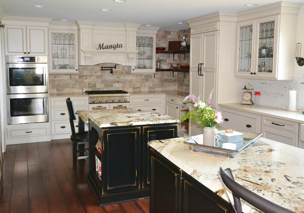 Huge elegant l-shaped dark wood floor and brown floor eat-in kitchen photo in Philadelphia with a farmhouse sink, recessed-panel cabinets, white cabinets, granite countertops, beige backsplash, stone tile backsplash, stainless steel appliances, two islands and multicolored countertops