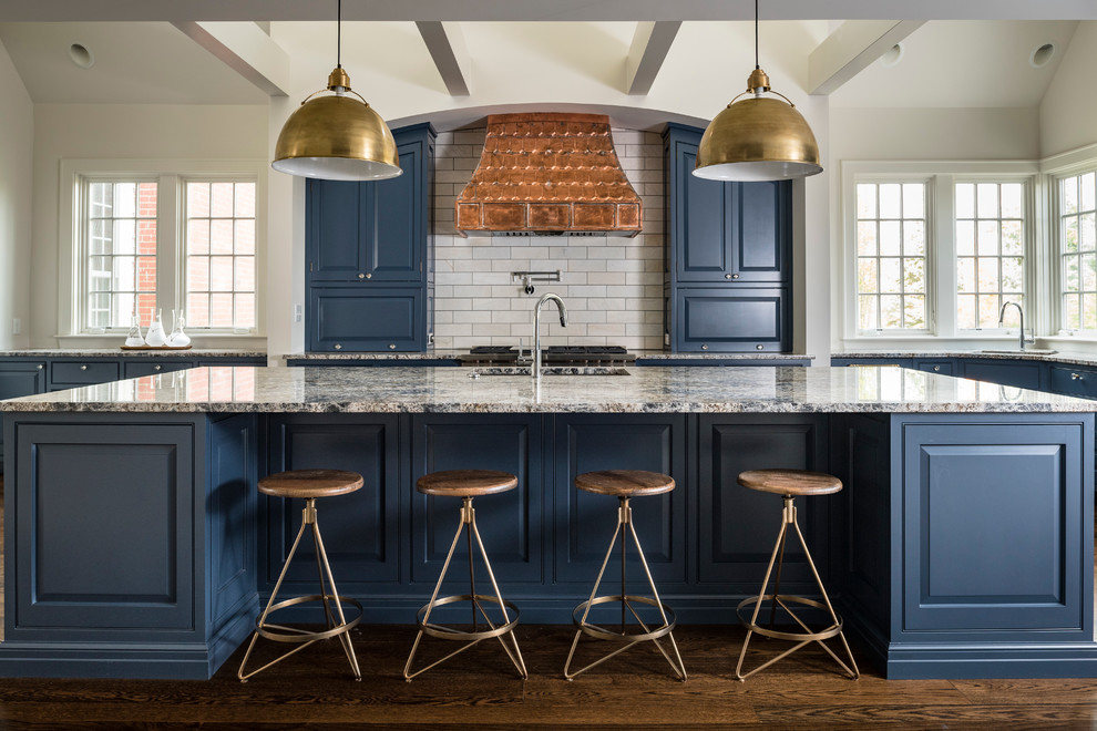 Mid-sized trendy l-shaped dark wood floor and brown floor open concept kitchen photo in Cincinnati with raised-panel cabinets, blue cabinets, subway tile backsplash, an island, a double-bowl sink, granite countertops, white backsplash, paneled appliances and gray countertops