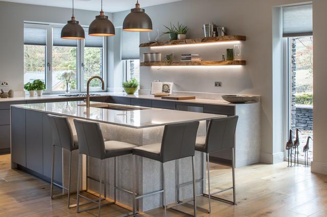 Esempio di una cucina a L minimalista con lavello sottopiano, ante lisce, ante grigie, parquet chiaro, isola, pavimento beige e top bianco