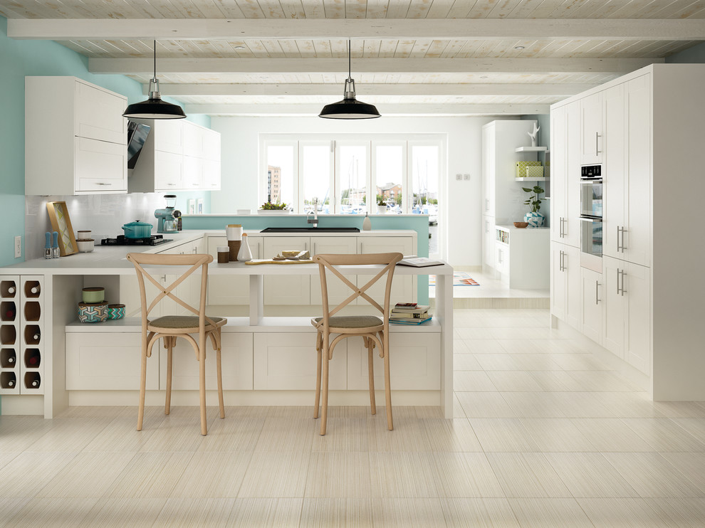 Eat-in kitchen - transitional u-shaped porcelain tile eat-in kitchen idea in Boise with white cabinets, a drop-in sink, shaker cabinets, quartz countertops, white backsplash, subway tile backsplash, stainless steel appliances and a peninsula