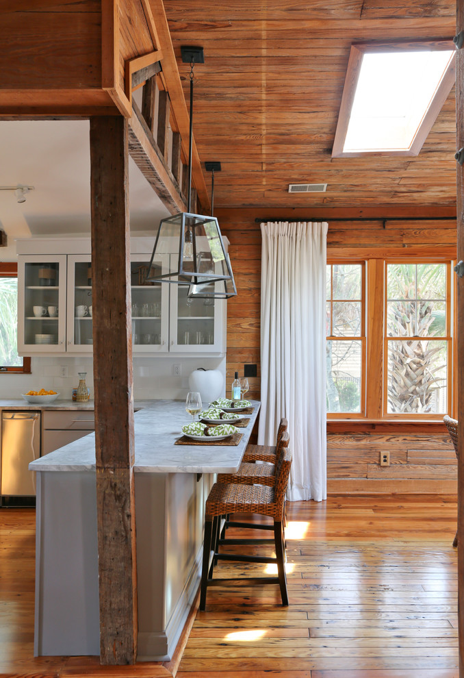 Eat-in kitchen - coastal eat-in kitchen idea in San Francisco with glass-front cabinets, white cabinets, white backsplash, subway tile backsplash and stainless steel appliances