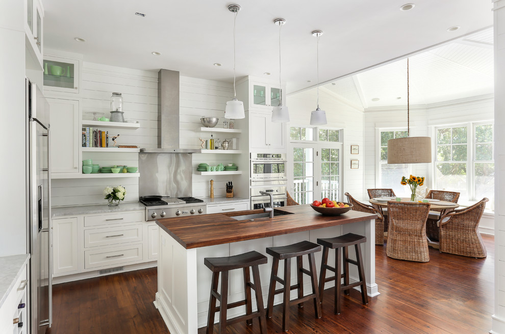 Example of a beach style eat-in kitchen design in San Francisco with an undermount sink, shaker cabinets, white cabinets, stainless steel appliances, wood countertops, metallic backsplash and metal backsplash