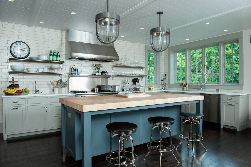 Example of a trendy kitchen design in New York with open cabinets, subway tile backsplash, wood countertops, white backsplash, gray cabinets and stainless steel appliances