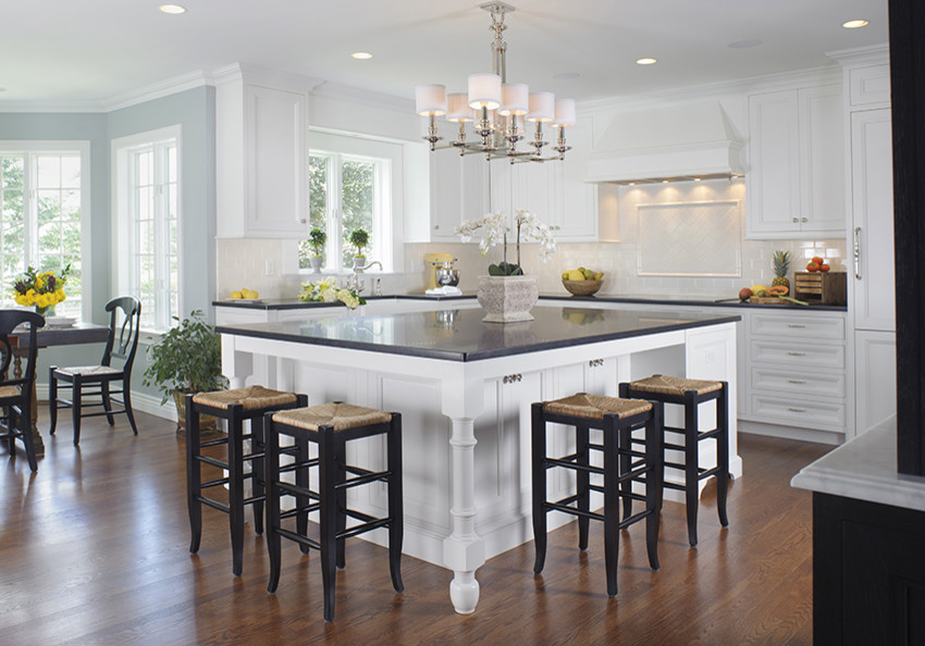 Eat-in kitchen - traditional l-shaped eat-in kitchen idea in Boston with a farmhouse sink, white cabinets, granite countertops, white backsplash, subway tile backsplash and paneled appliances