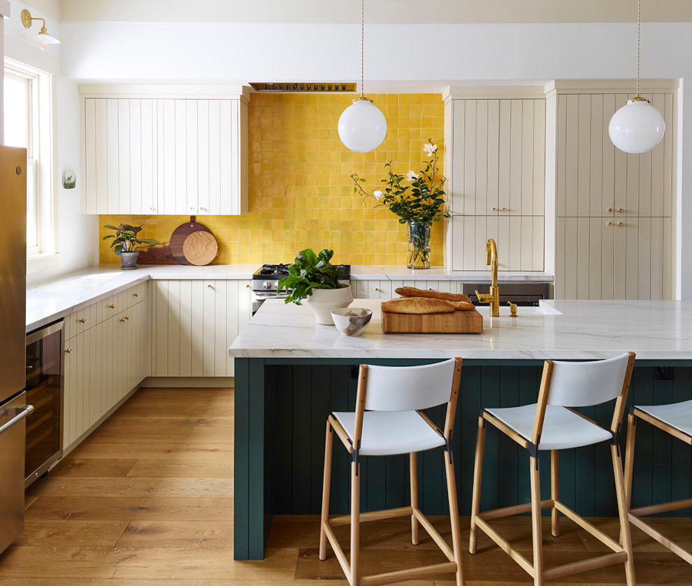 Large transitional l-shaped medium tone wood floor and brown floor eat-in kitchen photo in San Francisco with a farmhouse sink, flat-panel cabinets, beige cabinets, quartzite countertops, yellow backsplash, terra-cotta backsplash, stainless steel appliances, an island and white countertops