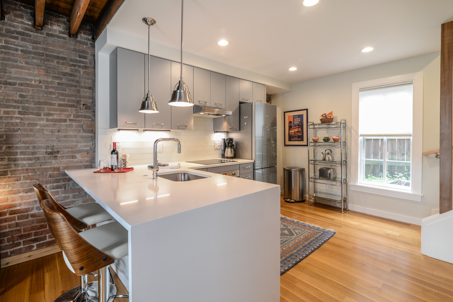 Inspiration for a small rustic l-shaped medium tone wood floor and brown floor eat-in kitchen remodel in Detroit with an undermount sink, flat-panel cabinets, gray cabinets, quartz countertops, white