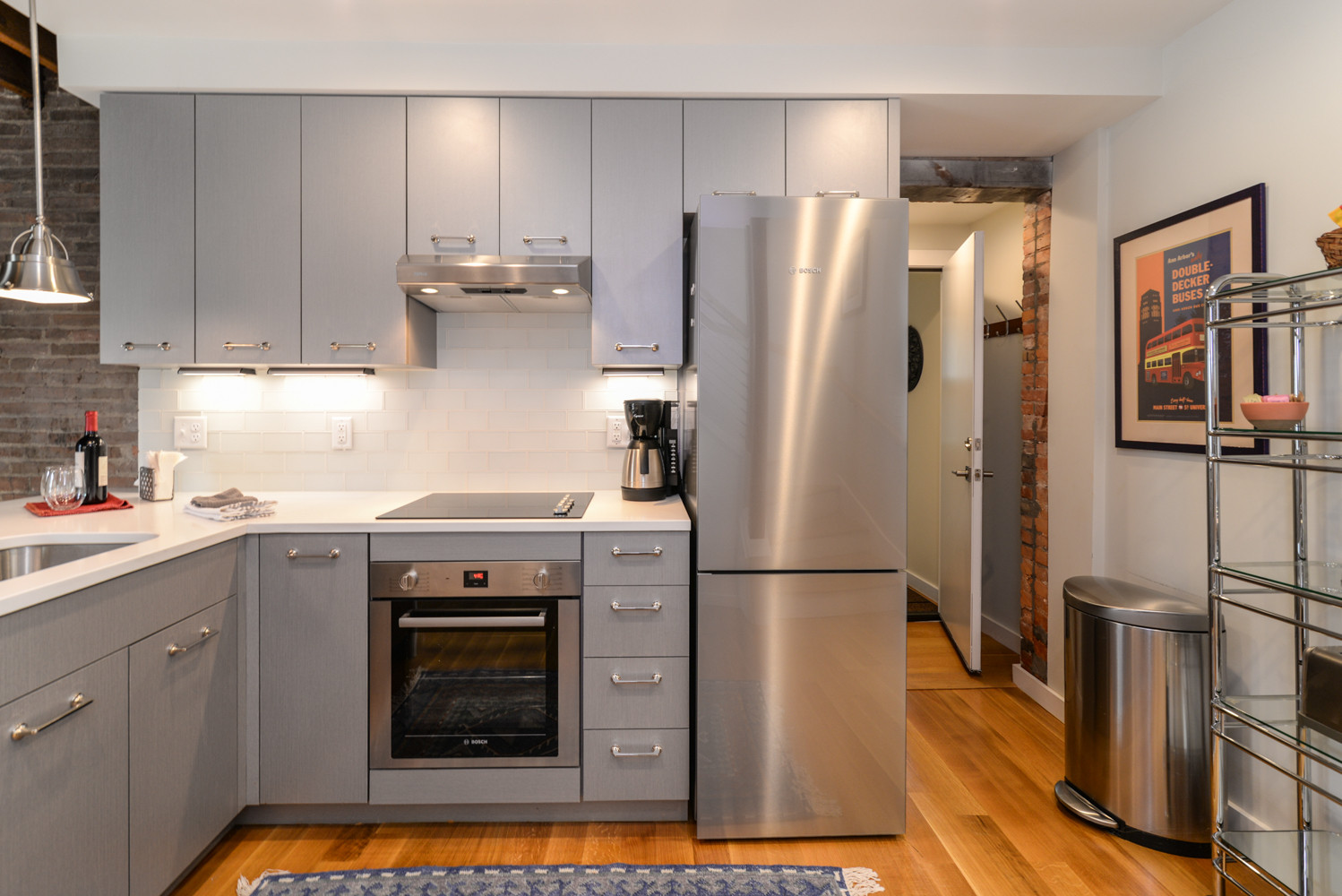 Eat-in kitchen - small rustic l-shaped medium tone wood floor and brown floor eat-in kitchen idea in Detroit with an undermount sink, flat-panel cabinets, gray cabinets, quartz countertops, white back