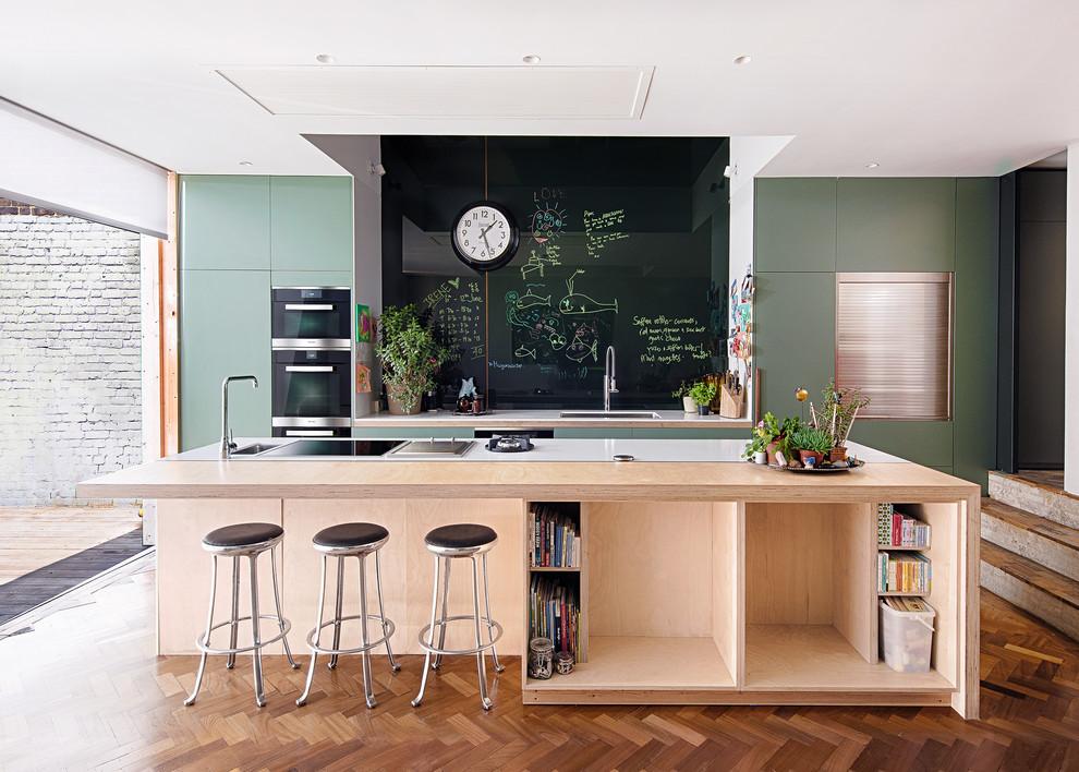 Cette image montre une cuisine parallèle design de taille moyenne avec un placard à porte plane, des portes de placards vertess, un sol en bois foncé, un îlot central, un sol marron, un évier encastré, une crédence noire et un électroménager en acier inoxydable.