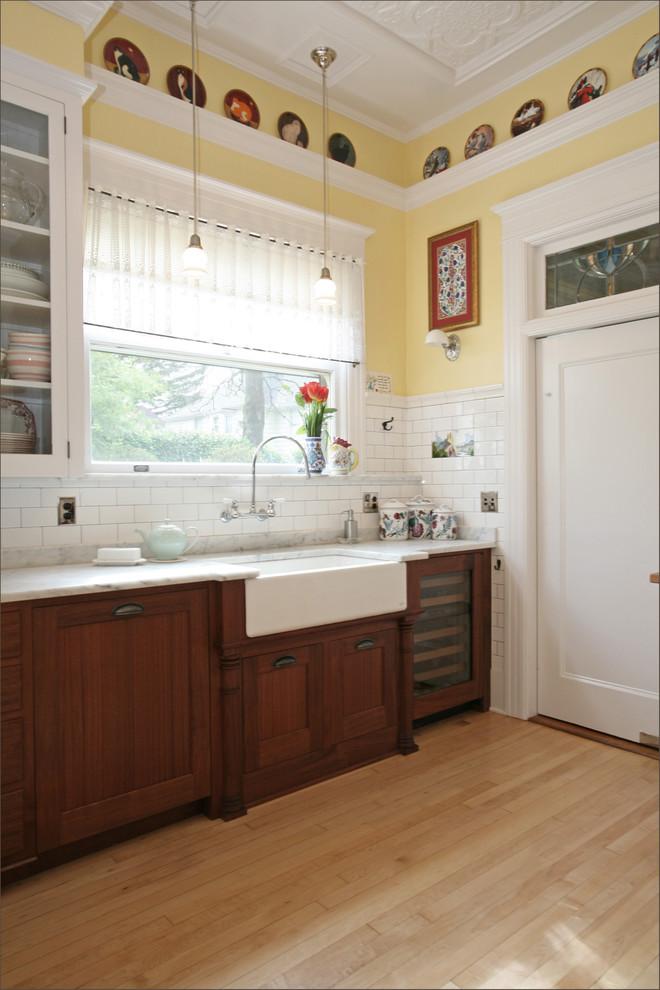 Kitchen - victorian kitchen idea in Portland with subway tile backsplash, marble countertops, a farmhouse sink, dark wood cabinets, white backsplash and paneled appliances