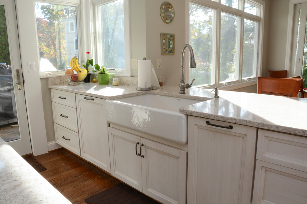Example of a large classic u-shaped medium tone wood floor open concept kitchen design in Baltimore with a farmhouse sink, recessed-panel cabinets, white cabinets, quartz countertops, multicolored backsplash, stainless steel appliances and an island