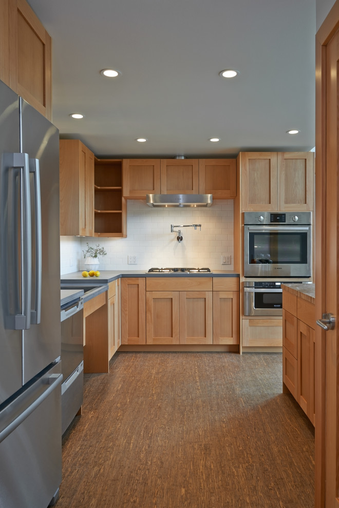 Example of a mid-sized transitional l-shaped bamboo floor and brown floor eat-in kitchen design in Seattle with shaker cabinets, light wood cabinets, white backsplash, subway tile backsplash, stainless steel appliances, a double-bowl sink, solid surface countertops and an island