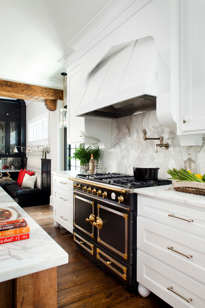 Example of a mid-sized classic l-shaped medium tone wood floor enclosed kitchen design in Atlanta with recessed-panel cabinets, white cabinets, white backsplash, stone slab backsplash, black appliances, marble countertops, an undermount sink and an island