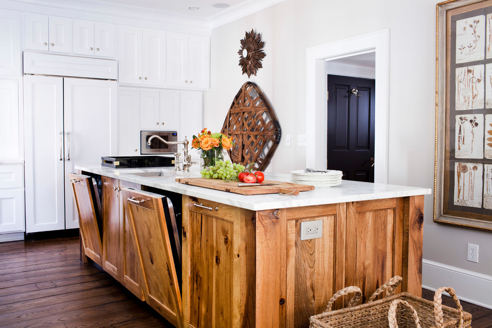 Inspiration for a mid-sized timeless l-shaped medium tone wood floor enclosed kitchen remodel in Atlanta with paneled appliances, an undermount sink, recessed-panel cabinets, white cabinets, marble countertops, white backsplash and an island