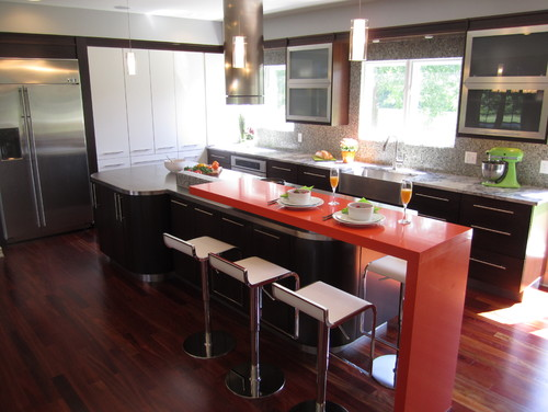 Black, White and Orange moderne kitchen design with aluminum framed cabinet doors and a breakfast bar kitchen island.