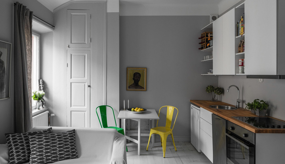 Inspiration for a small scandinavian single-wall painted wood floor open concept kitchen remodel in Stockholm with a drop-in sink, flat-panel cabinets, white cabinets, wood countertops, stainless steel appliances and no island