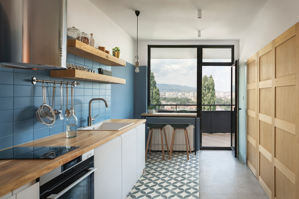 Trendy single-wall multicolored floor enclosed kitchen photo in London with a drop-in sink, flat-panel cabinets, white cabinets, wood countertops, blue backsplash, stainless steel appliances, no island and beige countertops