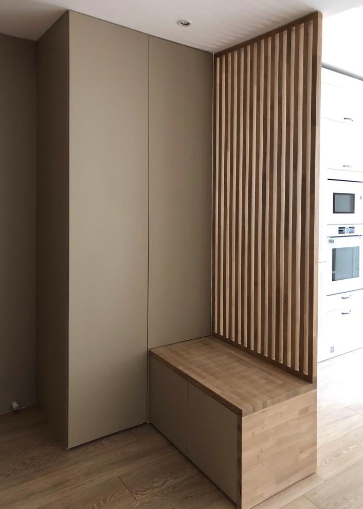 Aménagement d'une grande cuisine ouverte linéaire classique avec un évier encastré, un placard à porte affleurante, des portes de placard blanches, un plan de travail en stratifié, un électroménager blanc, un sol en bois clair, un îlot central, un sol marron et un plan de travail marron.