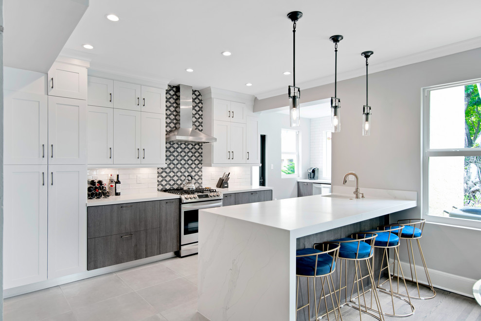 Mid-sized transitional u-shaped porcelain tile and gray floor open concept kitchen photo in Miami with a farmhouse sink, shaker cabinets, white cabinets, quartz countertops, stainless steel appliances, a peninsula and white countertops