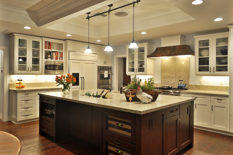 Example of a classic kitchen design in Phoenix with paneled appliances, glass-front cabinets, white cabinets, granite countertops, beige backsplash and stone slab backsplash