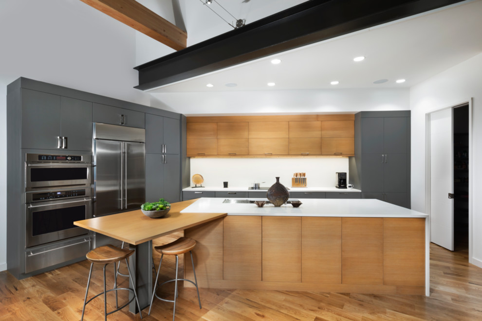 Photo of a contemporary galley kitchen in Other with flat-panel cabinets, grey cabinets, stainless steel appliances, medium hardwood flooring, an island and brown floors.