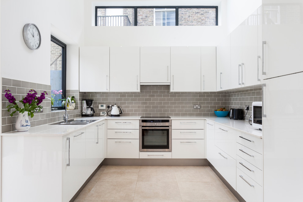 Inspiration for a contemporary u-shaped kitchen remodel in London with an undermount sink, flat-panel cabinets, white cabinets, gray backsplash, subway tile backsplash, stainless steel appliances and no island