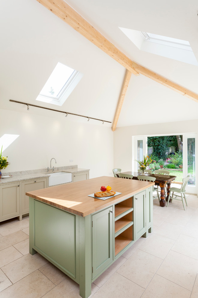 Example of a cottage eat-in kitchen design in London with a farmhouse sink, shaker cabinets and an island