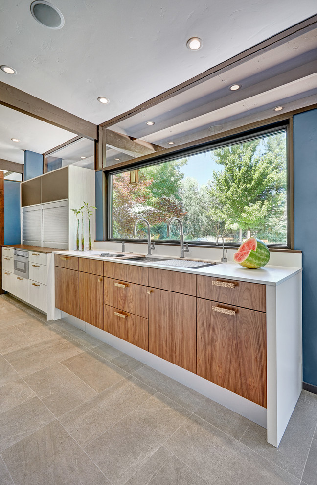 Mid-sized 1950s l-shaped porcelain tile and gray floor open concept kitchen photo in Sacramento with an undermount sink, flat-panel cabinets, white cabinets, quartz countertops, white backsplash, stone slab backsplash, white appliances and an island