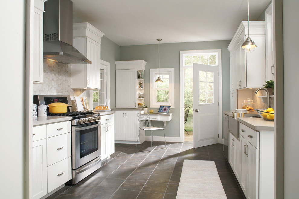 Inspiration for a large timeless galley ceramic tile eat-in kitchen remodel in Indianapolis with a farmhouse sink, stainless steel appliances, beaded inset cabinets, white cabinets, quartz countertops, gray backsplash, subway tile backsplash and a peninsula