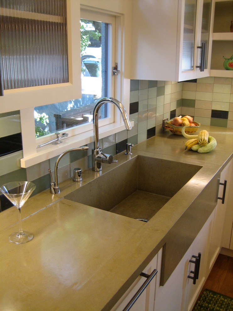 Mid-sized minimalist u-shaped medium tone wood floor eat-in kitchen photo in San Francisco with recessed-panel cabinets, white cabinets, concrete countertops, glass tile backsplash, stainless steel appliances, an island and an integrated sink
