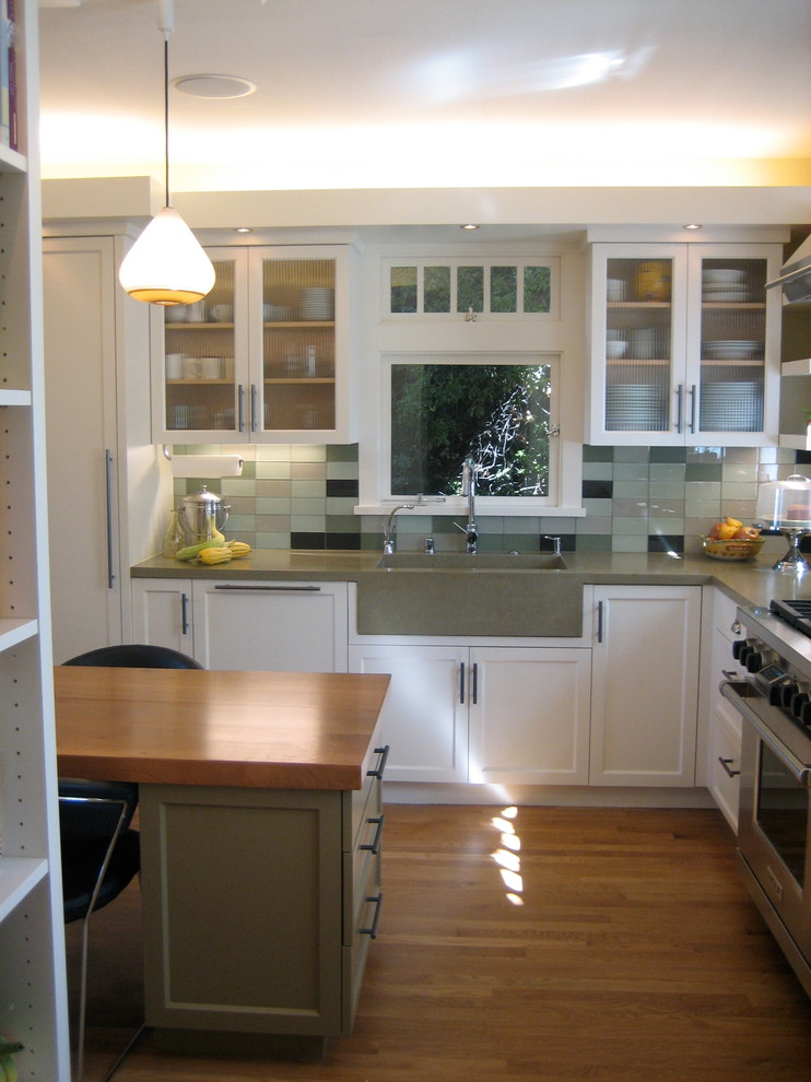 Inspiration for a mid-sized modern u-shaped medium tone wood floor eat-in kitchen remodel in San Francisco with a single-bowl sink, recessed-panel cabinets, white cabinets, concrete countertops, glass tile backsplash, stainless steel appliances and an island