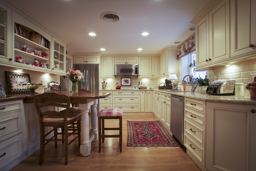 Enclosed kitchen - traditional l-shaped enclosed kitchen idea in Boston with stainless steel appliances, beige cabinets, granite countertops, white backsplash and subway tile backsplash