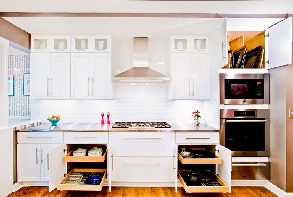 Mid-sized transitional single-wall medium tone wood floor eat-in kitchen photo in Chicago with shaker cabinets, white cabinets, white backsplash, subway tile backsplash, stainless steel appliances and stainless steel countertops