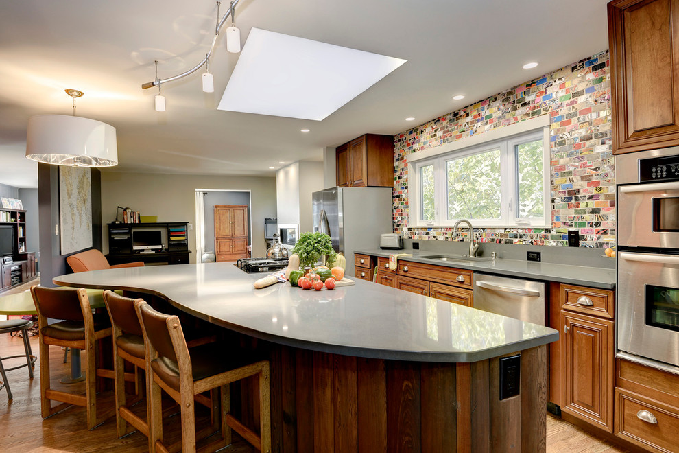 Mid-sized trendy single-wall medium tone wood floor eat-in kitchen photo in DC Metro with an undermount sink, raised-panel cabinets, medium tone wood cabinets, quartz countertops, multicolored backsplash, stainless steel appliances and two islands