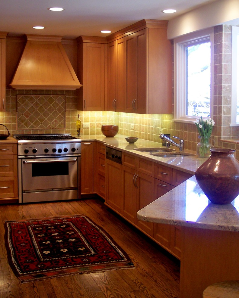 Mid-sized transitional l-shaped dark wood floor and brown floor kitchen photo in Chicago with a double-bowl sink, recessed-panel cabinets, medium tone wood cabinets, granite countertops, beige backsplash, stone tile backsplash, stainless steel appliances and a peninsula