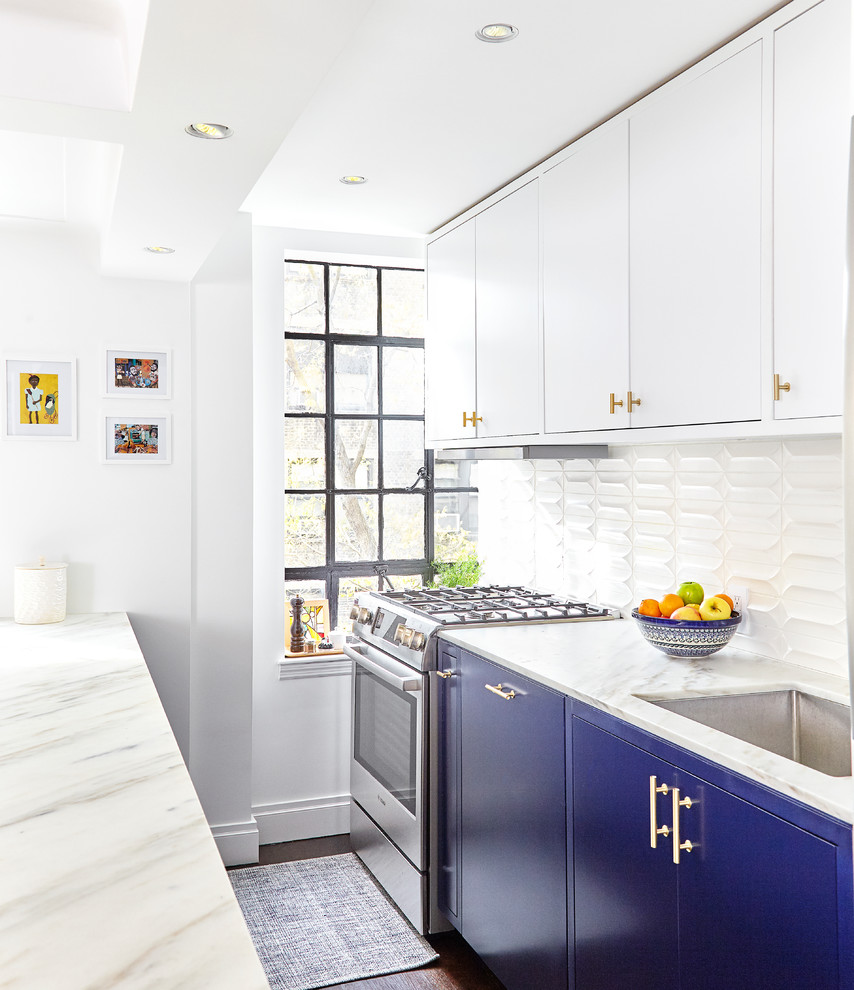 Small transitional galley dark wood floor and brown floor open concept kitchen photo in New York with an undermount sink, flat-panel cabinets, marble countertops, white backsplash, ceramic backsplash, stainless steel appliances, an island and blue cabinets