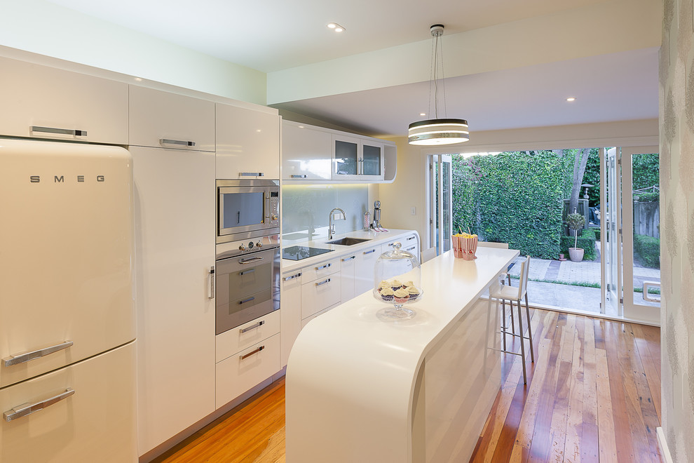 Kitchen - modern single-wall kitchen idea in Auckland with an undermount sink, flat-panel cabinets, white cabinets, glass sheet backsplash and white appliances
