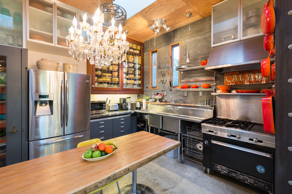 Example of an eclectic l-shaped concrete floor enclosed kitchen design in San Francisco with a double-bowl sink, glass-front cabinets and stainless steel appliances