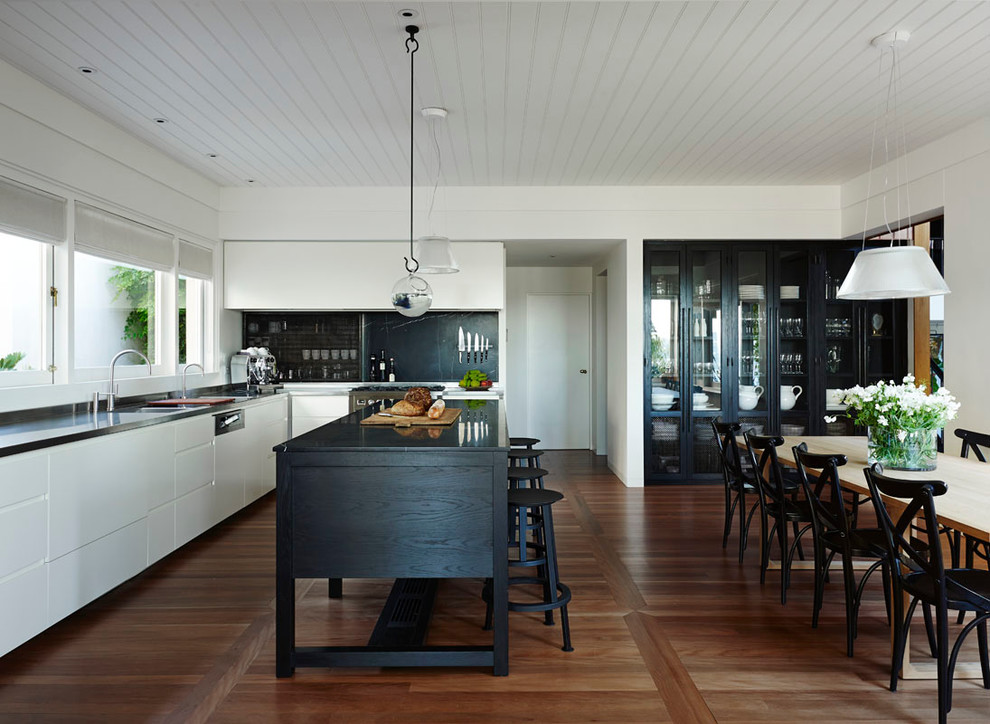 Example of a trendy l-shaped medium tone wood floor eat-in kitchen design in Sydney with a double-bowl sink, flat-panel cabinets, white cabinets, stainless steel appliances and an island