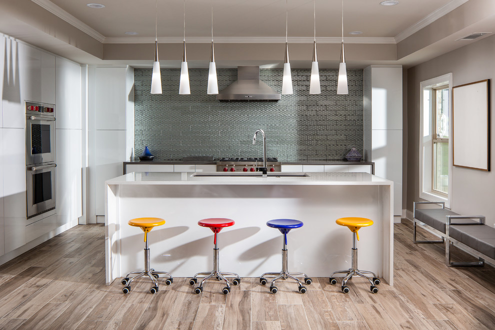 Inspiration for a mid-sized contemporary l-shaped porcelain tile and brown floor kitchen remodel in Atlanta with an undermount sink, flat-panel cabinets, white cabinets, metallic backsplash, metal backsplash, stainless steel appliances, an island, white countertops and quartzite countertops